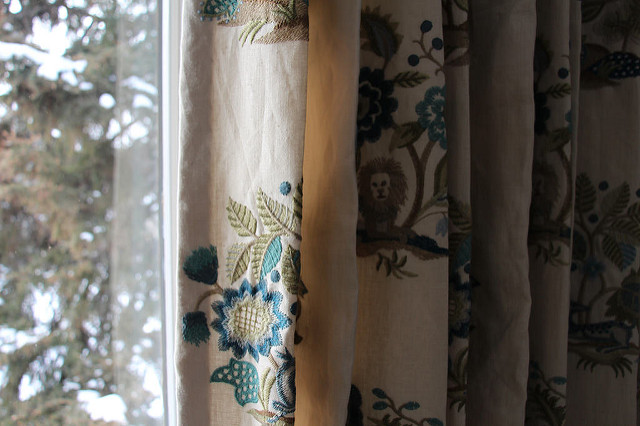Detail of custom pleated draperies with a linen blend fabric that has lions and floral elements in shades of blue.