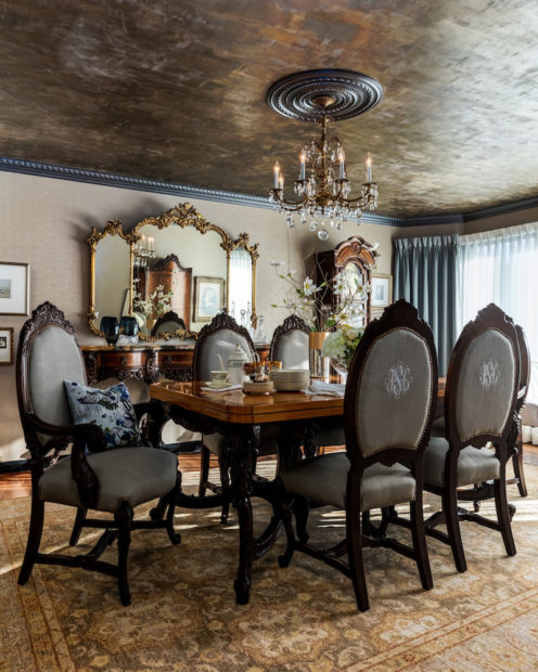 Dramatic dining room with an ornate gold mirror and special gold leaf treatment on the ceiling over reupholstered classic dining chairs with owners monogram embroidered onto the linen fabric.