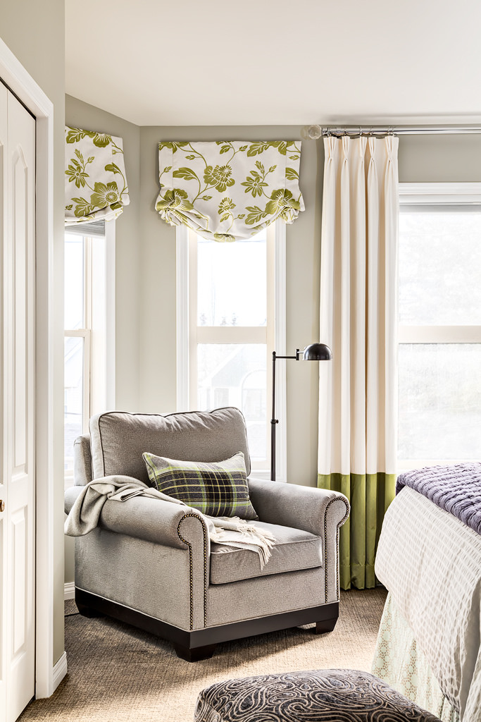 Sunny reading corner in a 2nd floor bedroom with many windows treated with custom valances in a lime green floral and floor to ceiling custom draperies.