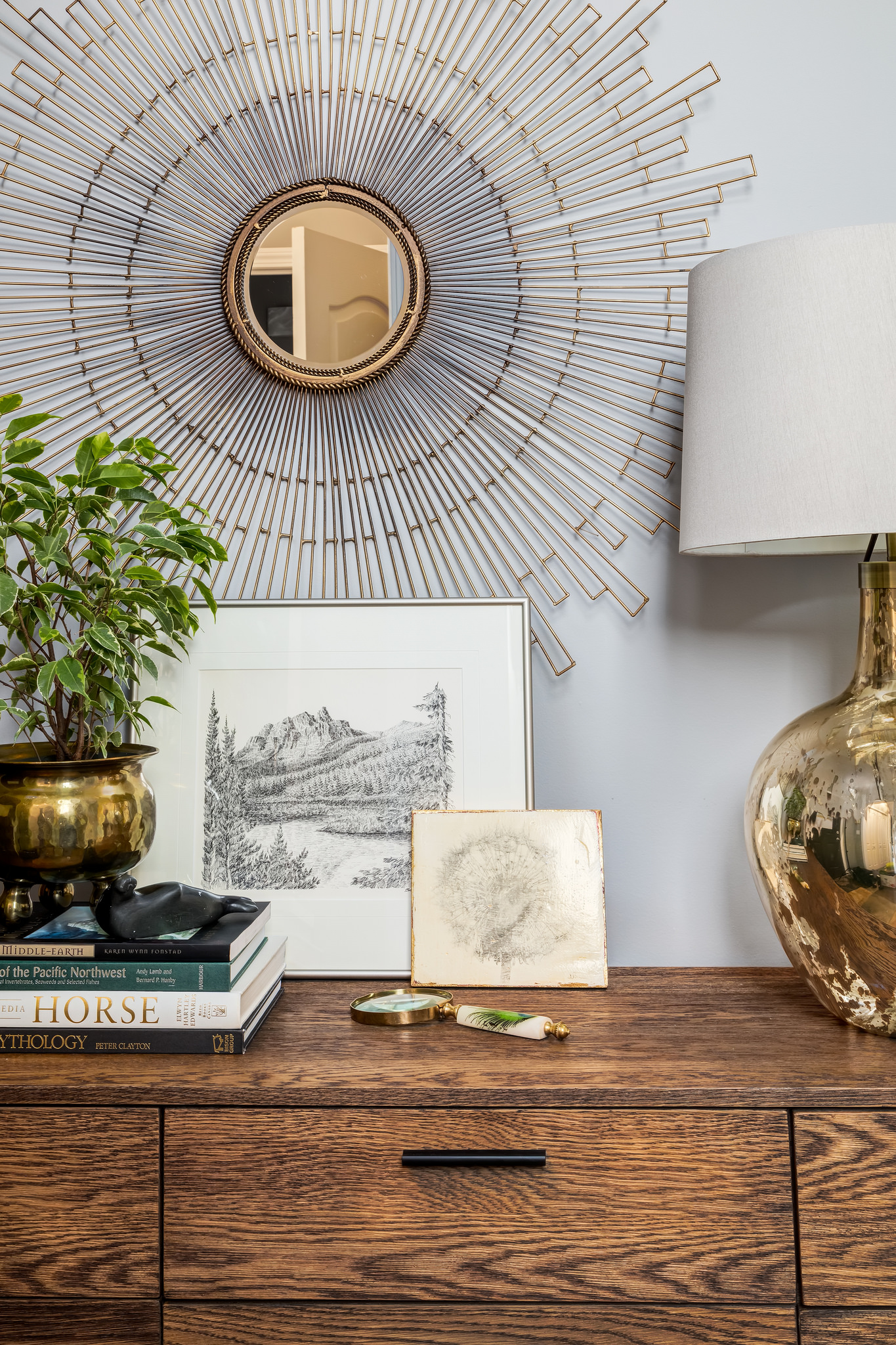 Collection of artifacts and art on a mid century console chest with a gold stardust mirror and a reflective gold lamp.