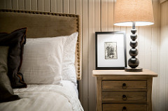 Detail shot of a clean white bed with rustic upholstered headboard against bead board walls.