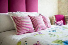 Custom designed hot pink upholstered headboard makes a watercolour pastel vintage wallpaper from the 80's look like it belongs there - interior design tricks.
