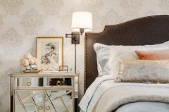 Luxury finishes in a feminine bedroom with a mirrored side chest and custom upholstery headboard.