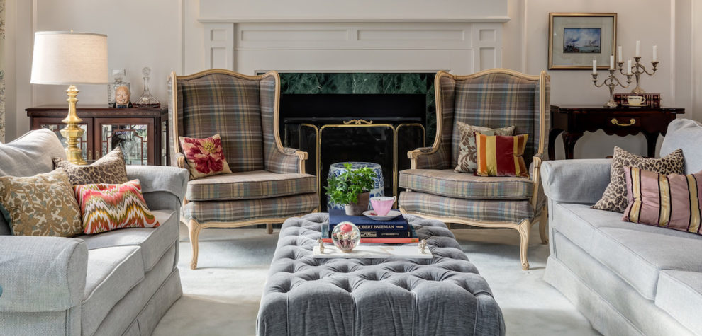 A restored wing back chair with a classic plaid fabric in a traditional living room in front of a beautiful fireplace and wainscotted wall.