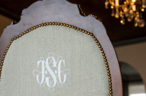 Embroidered monogram on the back of a restored mahogany chair with linen upholstery.