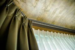 Layered window treatment with duponi silk pleated drapes layered over pleated sheers with a luxury carved moulding and artistically painted celiling.